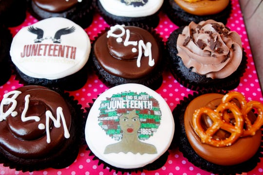 A customer picks up a batch of Juneteenth-themed cupcakes from Smallcakes Cupcakery & Creamery June 19, 2020.