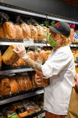 Maggie Catherwood stocks bread near the bakery during Earth Fare's first day of reopening June 22, 2020.