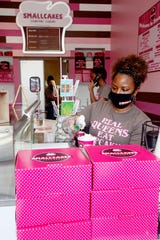 Brandy Mills, owner of Smallcakes, scoops ice cream for a customer as Jillian Brown answers the shop's phone June 19, 2020.