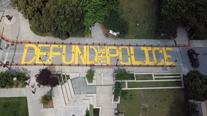 """Protesters painted """"Defund the Police"""" on Spruce Street in downtown Asheville June 21, 2020."""