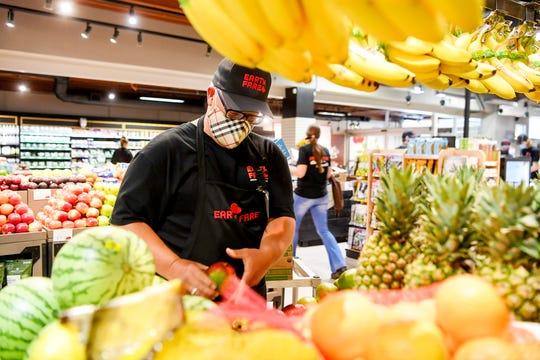 """Brian Sayles stocks fresh fruit on Earth Fare's first day of reopening June 22, 2020. Sayles said he was excited when he heard of the reopening. """"I'm very passionate about the food and what we bring here. You feel good about what you're eating,"""" he said, """"Plus, I love helping people."""""""