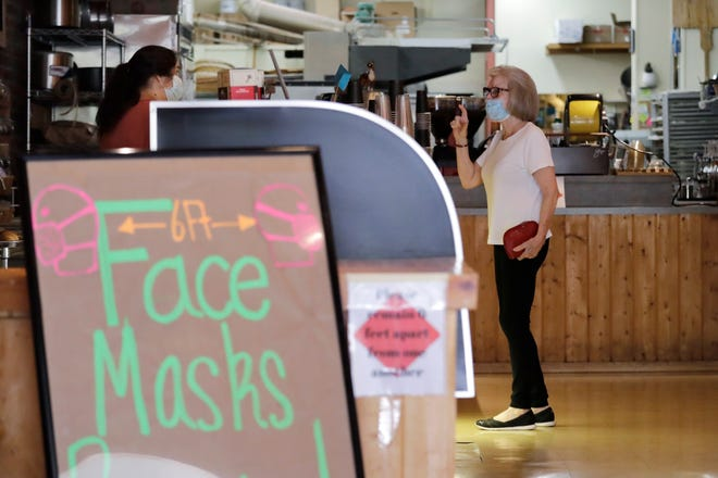 A customer, wearing a mask because of the coronavirus outbreak, puts in an order at a bakery Wednesday, June 17, 2020, in Yakima. Yakima, Benton and Franklin counties remain in Phase 1, meaning only essential businesses are open; restaurant service is limited to takeout and delivery; and limited outdoor recreation. (AP Photo/Elaine Thompson)