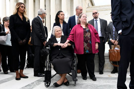 FILE - In this Oct. 8, 2019, file photo, Aimee Stephens, seated center, and her wife Donna Stephens, in pink, listen during a news conference outside the Supreme Court in Washington. Aimee Stephens lost her job when she told Thomas Rost, owner of the Detroit-area R.G. and G.R. Harris Funeral Homes, that she had struggled with gender identity issues almost her whole life. The Supreme Court has ruled that a landmark civil rights law protects gay, lesbian and transgender people from discrimination in employment. It's a resounding victory for LGBT rights from a conservative court.  Laverne Cox, the award-winning transgender actress and longtime trans rights activist, listens at left. (AP Photo/Susan Walsh, File)