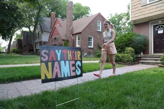 Christina Krysiak with one of her Say Their Names signs she has been selling Friday, June 18, 2020.