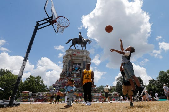 Isaiah Bowen, right, takes a shot as his dad, Garth Bowen, center, looks on at a basketball hoop in front of the statue of Confederate General Robert E. Lee on Monument Avenue Sunday in Richmond, Va. (AP Photo/Steve Helber)