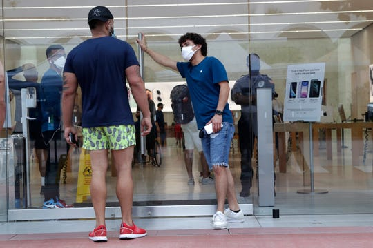An employee wearing a protective face covering, right, monitors the flow of customers at an Apple retail store along Lincoln Road Mall during the new coronavirus pandemic, Wednesday in Miami Beach, Fla.