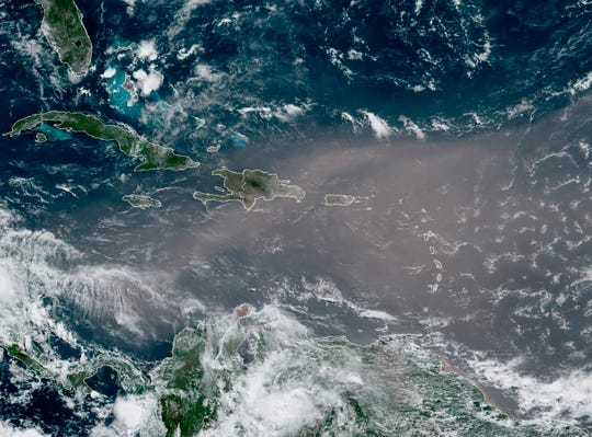 A satellite photo from NOAA shows a cloud of dust coming from the Sahara desert arriving over the Caribbean on Monday, June 22, 2020. The massive cloud of dust is blanketing the Caribbean as it heads to the U.S. with a size and concentration level that meteorologists say hasn't been seen in roughly half a century.