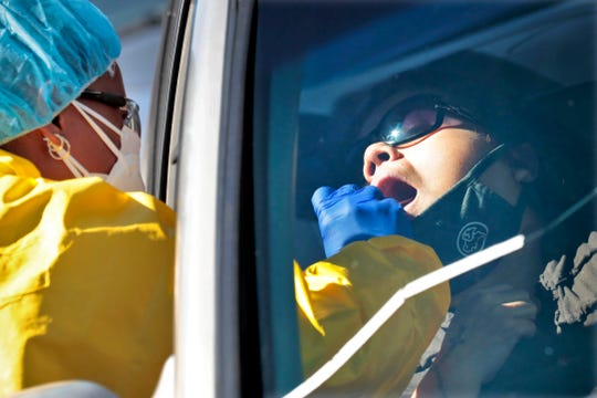 People get tested for COVID-19 at a drive through testing site hosted by the Puente Movement migrant justice organization Saturday, June 20, 2020, in Phoenix.