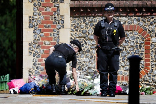 A Police officer places flowers from a woman at the scene of a fatal multiple stabbing attack in Forbury Gardens, central Reading, England, Monday June 22, 2020. A lone terror suspect remains in custody accused of killing three people and wounding three others in a Reading park on Saturday night.