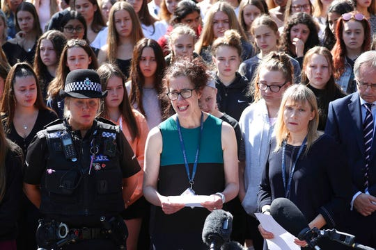 Co-Headteacher Anne Kennedy, centre, speaks to media as colleagues and pupils of teacher James Furlong stand together to take part in a period of silence at the Holt School, in Wokingham, England, in memory of teacher James Furlong, a victim of a terror attack in nearby Reading, Monday June 22, 2020.