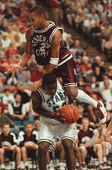 Henderson County's Ervin Miller (42) goes over the back of Muhlenberg North's J.R. Reynolds (52) and is called for a foul during the 1999 Sweet 16 at Rupp Arena.