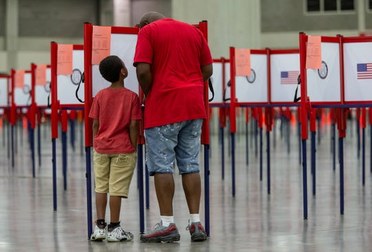 Carreon Johnson 8, looks up at his father, Dechareon, as he votes early on Monday in the Kentucky primary election at the expo enter in Louisville. June 22, 2020