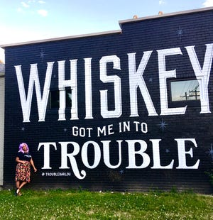 Felicia Corbett, new assistant beverage director at Trouble Bar, stands in front of its mural on Shelby Street.