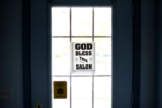 """A sign reading """"God bless this salon,' is displayed on the door of Braids and Things International on Friday, June 19, 2020, in Lansing."""
