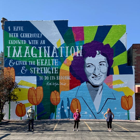 Artists pose with the new Ruth West mural on the Milwaukee PC building in downtown Manitowoc.