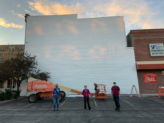 Artists prepare to paint the Ruth West mural on the Milwaukee PC building in downtown Manitowoc.