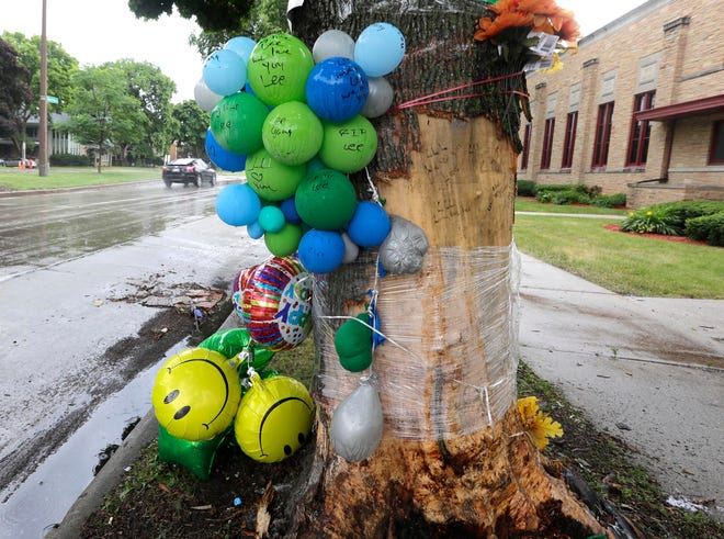 A memorial is seen on a tree where a 34-year-old woman died when the vehicle she was in lost control and hit a tree in the 3700 block of North Sherman Boulevard around 3:45 a.m. Sunday.