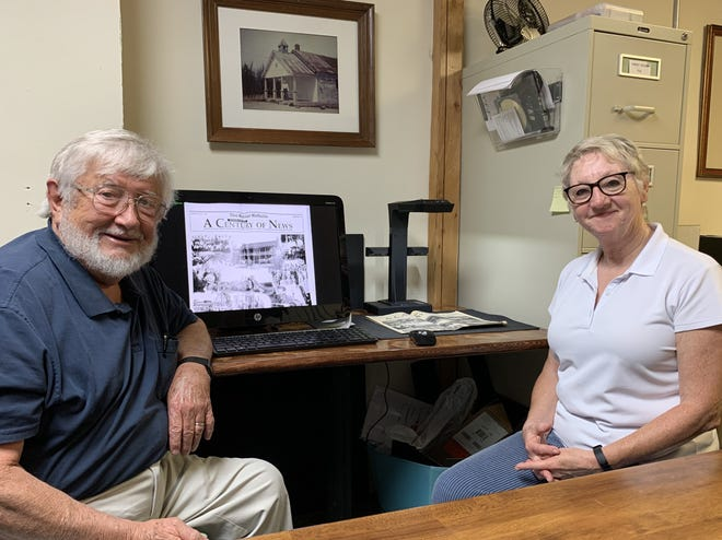 David Benedict, President of the Baxter County Historical Society shows Gwen Khayat, Director of Twin Lakes Community Foundation, the new book scanner provided by a $600 grant from the Foundation.