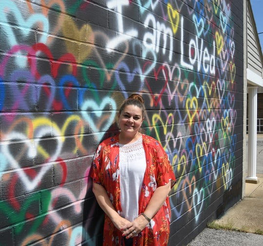 Natalie Slusser stands next to the #iamlovedwall, which she completed last year.