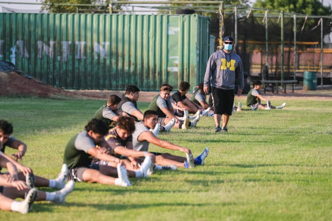 The Mayfield football team stretch six feet apart in their first practice in Las Cruces on Monday, June 22, 2020.