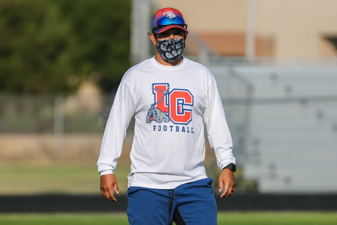 Coaches wear masks as the Las Cruces High School football team run drills in Las Cruces on Monday, June 22, 2020.