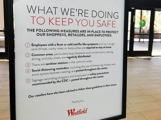 A sign regarding COVID-19 safety precautions and guidelines sits inside Westfield mall on Monday, June 22, 2020 in Palm Desert, Calif.