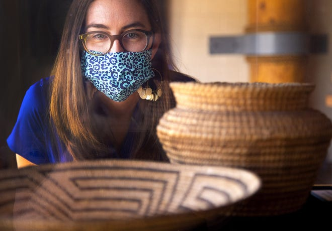 Emily Goble Early, curator of anthropology at Arizona Museum of Natural History, looks at some basketry plate and jar from the Akimel O'odham at the Mesa Grande Cultural Park. The Arizona Museum of Natural History received a grant to research and document some items in their collection that may turn out to be funerary or ceremonial and need to be repatriated to a tribe.