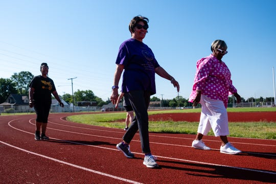 Pastor Kim Brown, of Zion Cathedral of Praise in Port Huron, left, walks with Sadie Russell, right, and Janie Williams Friday, June 19, 2020, at the track near Port Huron High School. Brown meets with members of her church several times a week to walk laps on the track.