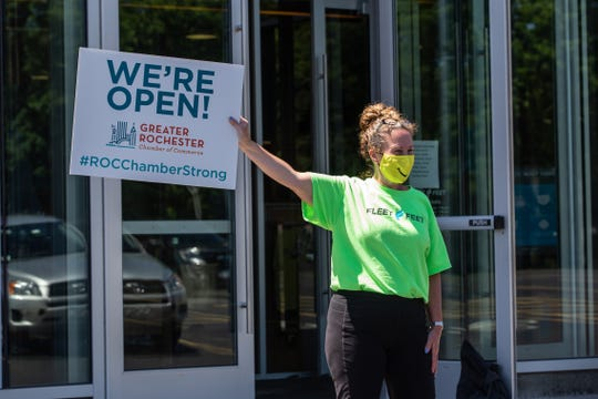 Ellen Brenner, co-owner of Fleet Feet Rochester, holds up a sign on Wednesday, June 17, 2020, as she's recorded by someone from the Greater Rochester Chamber of Commerce for a video for social media about businesses that have re-opened after the COVID-19 shutdown.