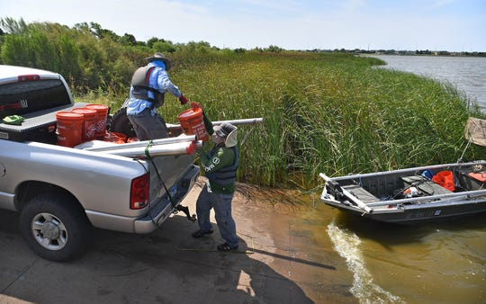 Tim Osting, left, and David Flores load samples of sediment taken from the bottom of Lake Wichita Monday morning. Approximately 1,000 pounds of samples are being gathered.