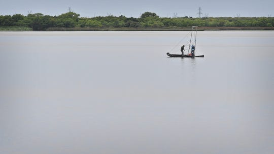 David Flores of Arroyo Environmental Consultants and Tim Osting of Aqua Strategies use a speccially-outfitted johnboat to take soil samples from the Lake Wichita sediment Monday.