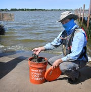 Tim Osting of Aqua Strategies shows a sample of lakebed sediment taken from Lake Wichita Monday. The sample will be analyzed to determine if it is suitable for making compressed earth blocks for construction.