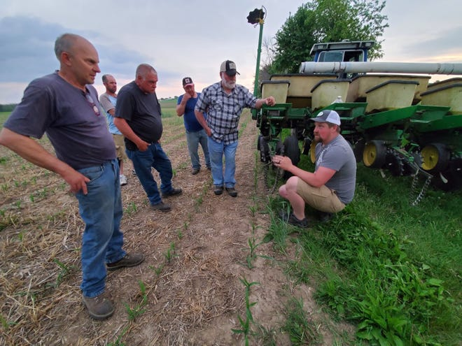 Jory Stapel, right, of Double Dutch Dairy in Cedar Grove, Wis., talks with other farmers during a Sheboygan River Progressive Farmers field day on June 2. The event was held at a crop farm owned by Joe Wagner, far left, who is president of the farmer-led watershed conservation group in Sheboygan County.