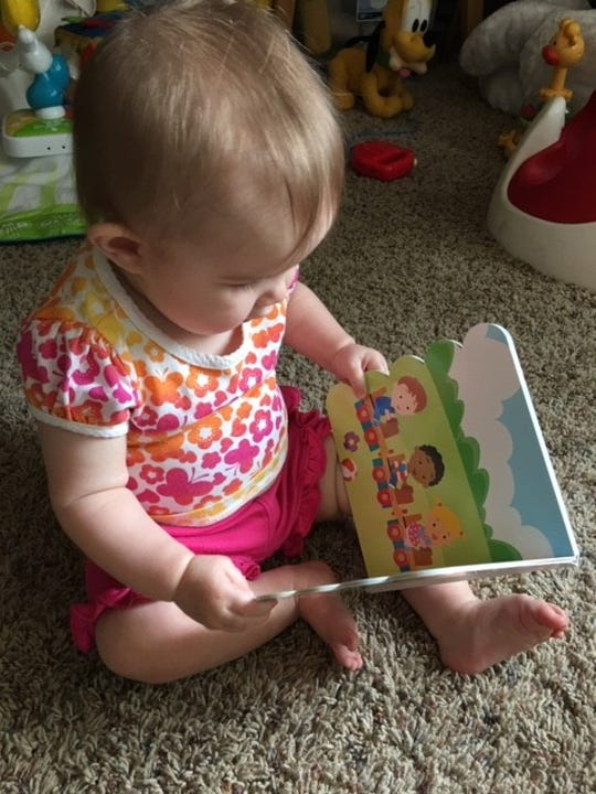 8-month-old Josie Riley, enjoys a book. The Muskingum County Literacy Council is working to provide free books to children in Muskingum County. There are more than 1,400 enrolled in the program which send books directly to the homes of children each month. Parents can sign up children by visiting, OhioImaginationLibrary.org.