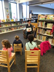 """Christine Wagner, dressed as Mary Poppins, read books to children at the John McIntire Library during the Muskingum County Literacy Council's """"Leap into Literacy"""" event held on Leap Day to celebrate the introduction of the Dolly Parton Imagination Library to Muskingum County. The program provides free monthly books to any child, from birth to age 5."""