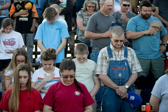 Race fans pray before an event in late May at Ace Speedway in Alamance County in North Carolina. A judge has left in place an injunction barring the speedway from holding races. The injunction was issued two weeks ago after the speedway defied restrictions on large crowds implemented to mitigate the spread of the new coronavirus.
