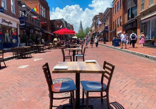 Restaurant set tables on Main street, closed to traffic, to create an outdoor dining area where people can enjoy lunch in Annapolis, Maryland, on June 21, 2020 - Visitors flock to Annapolis for the start of summer 2020 amid the coronavirus pandemic.