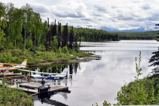 In this June 2, 2020, photo idle float planes sit at a lake near Talkeetna, Alaska.