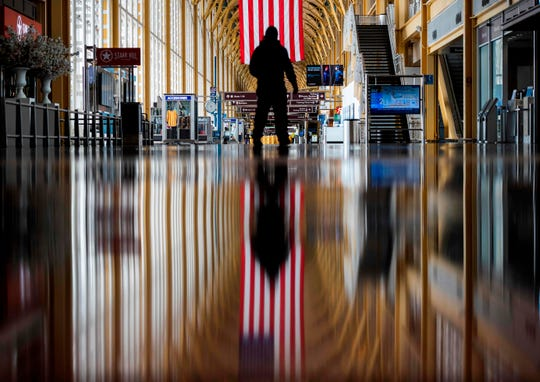 An airport employee walks through Ronald Reagan Washington National Airport. The airline industry has been hit hard by the COVID-19 pandemic, with the number of people flying drastically decreasing.
