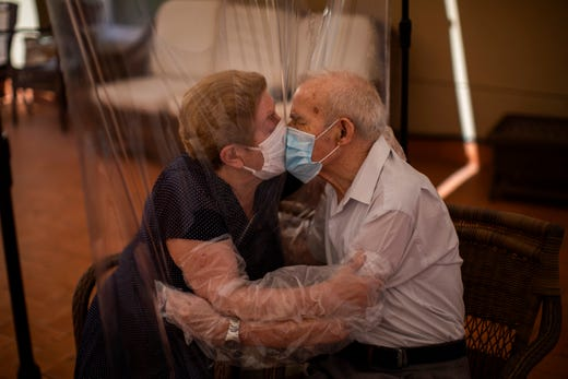 Agustina Cañamero, 81, and Pascual Pérez, 84, hug and kiss through a plastic film screen to avoid contracting the new coronavirus at a nursing home in Barcelona, Spain, Monday, June 22, 2020. The Ballesol Fabra i Puig elderly care center installed the screens to resume relatives' visits to residents 102 days after a strict, nationwide lockdown separated them. As she and her husband broke out into tears while kissing through layers of protective masks and the transparent plastic film, Cañamero said that the couple had never spent such long time with no physical contact in 59 years of marriage.