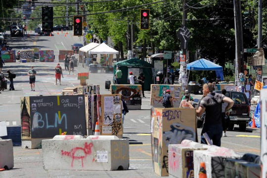 """People walk amidst barricades in what has been named the Capitol Hill Occupied Protest zone in Seattle Monday, June 22, 2020. For the second time in less than 48 hours, there was a shooting near the """"CHOP"""" area that has been occupied by protesters after Seattle Police pulled back from several blocks of the city's Capitol Hill neighborhood near the Police Department's East Precinct building."""