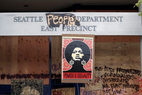 A 1970's-era poster of activist Angela Davis hangs at a boarded up and closed Seattle police precinct Sunday, June 21, 2020, in Seattle, where streets are blocked off in what has been named the Capitol Hill Occupied Protest zone. Police pulled back from several blocks of the city's Capitol Hill neighborhood near the Police Department's East Precinct building earlier in the month after clashes with people protesting the death of George Floyd, a Black man who died after being restrained by Minneapolis police officers on May 25.