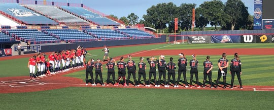 Players from the USSSA Pride, left, and the Houston Scrap Yard Dawgs get ready to stand for the National Anthem before Monday's softball game in Viera, Florida.