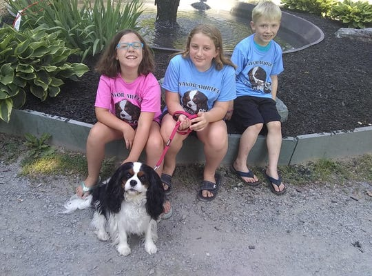 Murfee, the canine mayor of Fair Haven, poses with admirers (from left) Skye Schaumloffel, 8; Caitlin Schaumloffel, 10; and Dawson Grau, 7, in the town's park on June 23, 2020. The tee-shirts bearing Mayor Murfee's likeness are part of a fundraiser to rehabilitate the park's playground equipment.