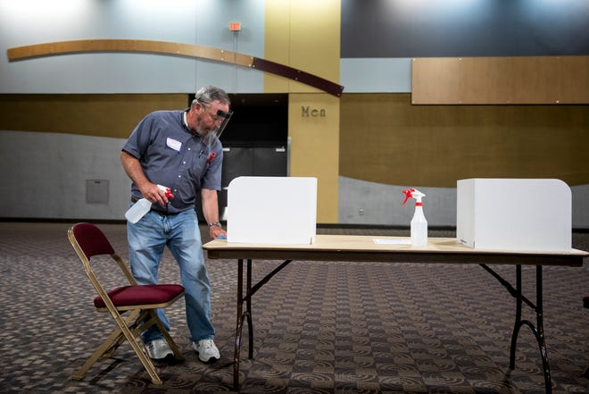 Tom Goetz, an election official, sanitizes a voting station during the Kentucky Primary election at the Northern Kentucky Convention Center on Tuesday, June 23, 2020 in Covington, Kentucky.