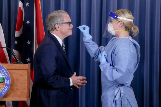 Ohio Gov. Mike DeWine gets tested by an Ohio National Guard nurse during his coronavirus briefing.