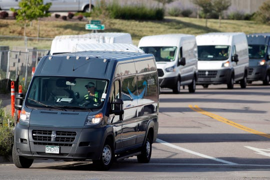 In this July 30, 2019, file photo, vans queue up to leave an Amazon delivery center in suburban Englewood, Colo.