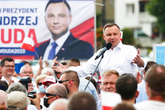 "Polish President Andrzej Duda waves to supporters as he campaigns for a second term in Serock, Poland, on Wednesday, June 17, 2020. Duda has made LGBT rights an issue during the campaign, vowing to protect Polish families from what he calls ""LGBT ideology."""