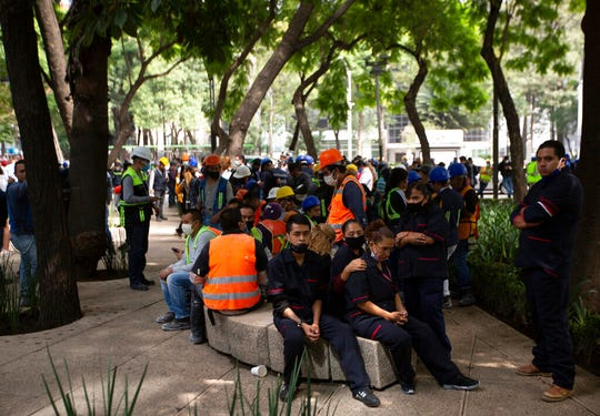 Employees gather outside of their work building after a 7.5 earthquake, in Mexico City, Tuesday, June 23, 2020. The earthquake centered near the resort of Huatulco in southern Mexico swayed buildings Tuesday in Mexico City and sent thousands into the streets.
