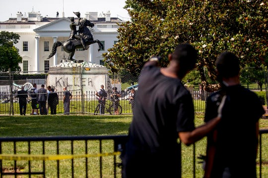 "Anthony Davis of Upper Marlboro, Md., left, speaks to his son Jonathan, 13, right, as they look at a statue President Andrew Jackson in Lafayette Park, Tuesday, June 23, 2020, in Washington, with the word ""Killer"" spray painted on its base. Protesters tried to topple the statue Monday night."